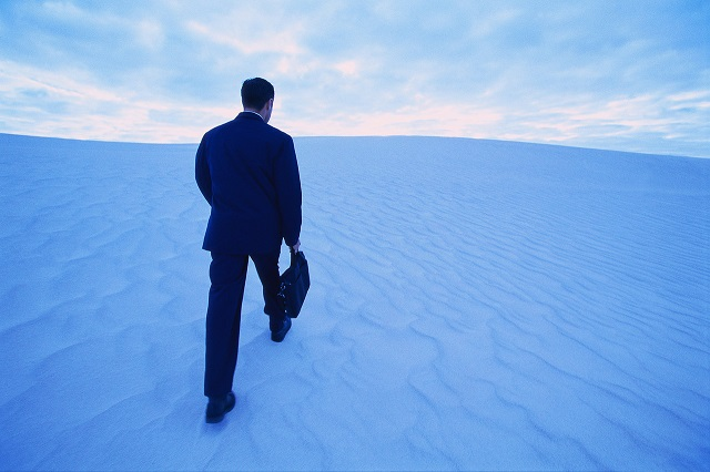 Businessman Walking up Sand Dune